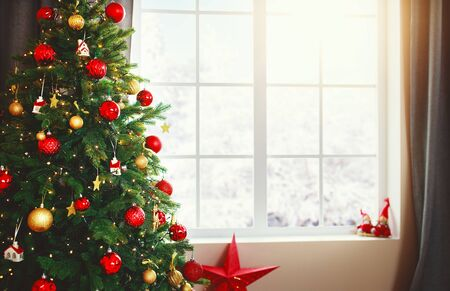 Foto per Christmas interior tree with gifts near the window at home  - Immagine Royalty Free