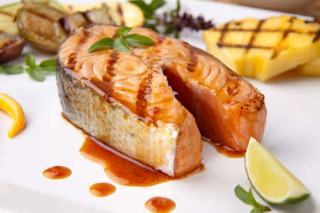 Delicious grilled Teriyaki salmon steak  garnished with grilled pineapple, baby eggplants, zucchini and chilli pepper for healthy style dinner.