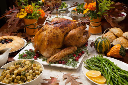 Photo for Roasted turkey garnished with cranberries on a rustic style table decoraded with pumpkins, gourds, asparagus, brussel sprouts, baked vegetables, pie, flowers, and candles. - Royalty Free Image
