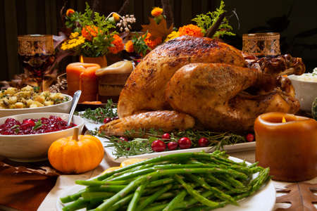 Photo pour Roasted turkey garnished with cranberries on a rustic style table decoraded with pumpkins, gourds, asparagus, brussel sprouts, baked vegetables, pie, flowers, and candles. - image libre de droit