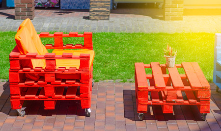 Photo for Table bench of pallets in the street sun green cafe - Royalty Free Image