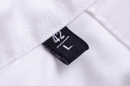 Foto de White shirt macro tag size L texture background - Imagen libre de derechos