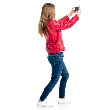 Foto de Beautiful woman in red jacket and jeans in hand smartphone selfie isolated on white background, back view - Imagen libre de derechos