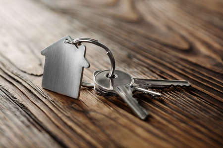 Foto de Symbol of house with silver key on wooden background - Imagen libre de derechos