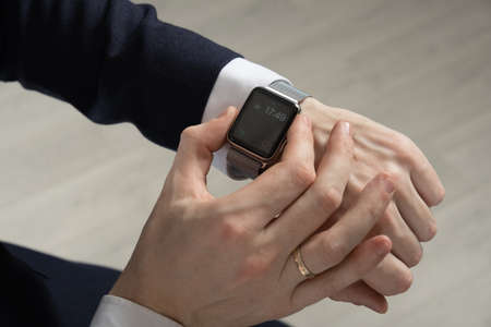 Foto per mens hands in a suit indicate a smart watch - Immagine Royalty Free
