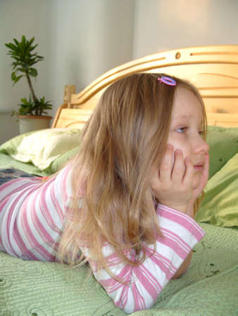 Thinking Girl. Affectionate age. Little girl lying on the bed.
