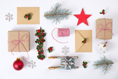 Photo for Christmas frame composition. Christmas gift, pine branch, red balls, envelope, white wood snowflakes, ribbon and red berries. Top view, flat lay, copy space - Royalty Free Image