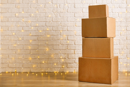 Foto de Stack of four blank brown freight boxes, different size, brick wall with Christmas lights on background. Moving company / delivery service holiday deals promotion concept. Copy space, close up. - Imagen libre de derechos