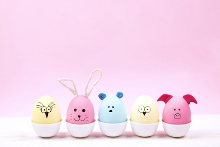 Funny childish easter eggs animals and birds characters with ears painted by child kid. Egg cup on white table and pink wall background.