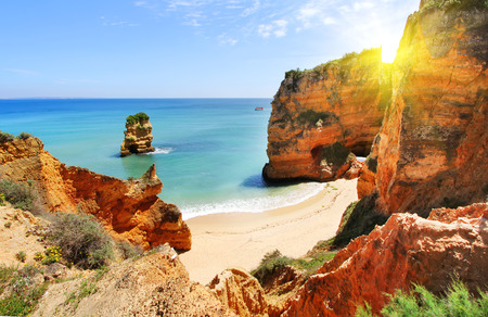 Foto de Rocky beach at sunset, Lagos, Portugal. Counter light. Travel and business background - Imagen libre de derechos