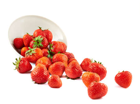 Scattered strawberries from a white ceramic bowl isolated over white background