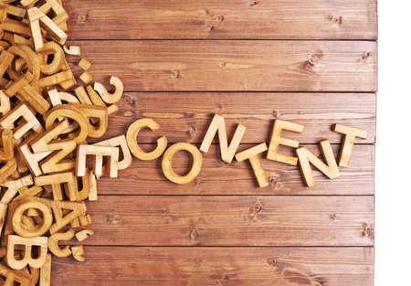Photo for Word content made with block wooden letters next to a pile of other letters over the wooden board surface composition - Royalty Free Image