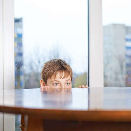 12 years old childen boy peeking out from the wooden desk table, composition against the window
