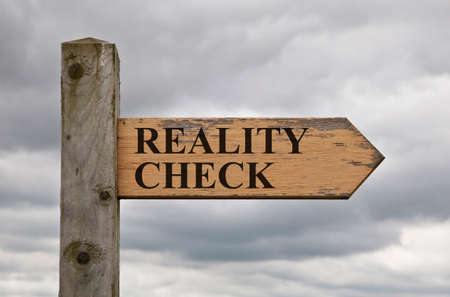 Foto de Grungy wooden reality check sign on a sign post against cloudy sky - Imagen libre de derechos