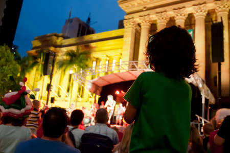 Kid stands to enjoy concert at night