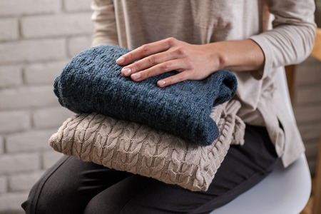 Photo pour Womans hands holding knitted clothes. Close up. Concept of cozy home. - image libre de droit