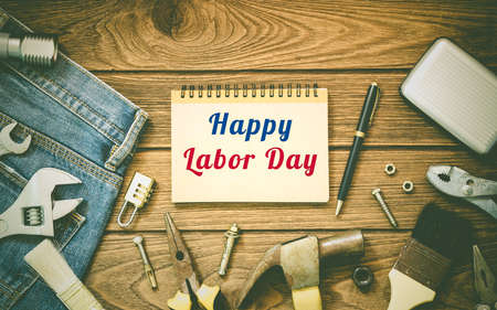 Photo pour Labor day background concept - Jeans, many handy tools, notebook with happy labor day text on wooden background top view - image libre de droit