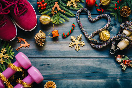 Photo pour Fitness, healthy and active lifestyles love concept, dumbbells, sport shoes, skipping rope or jump rope  in heart shape with Christmas decoration items on wood background. Exercise, Fitness and Working Out Merry Christmas and Happy new year concept. - image libre de droit