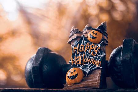 Foto de Halloween festival Close up of Halloween head Pumpkins doll and the black iron dumbbell. Fitness, healthy active lifestyle on Halloweeen day concept. - Imagen libre de derechos
