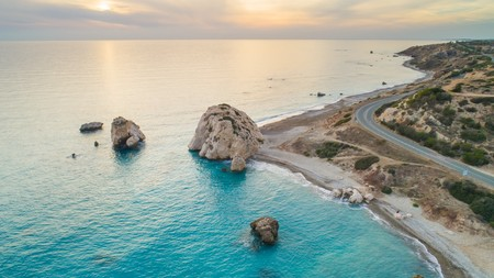 Foto de Aerial Bird's eye view of Petra tou Romiou, aka Aphrodite's rock a famous tourist travel destination landmark in Paphos, Cyprus. The sea bay of goddess Afroditi birthplace at sunset from above. - Imagen libre de derechos