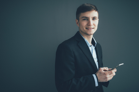 Smiling businessman leaning against a wall while using the smartphone