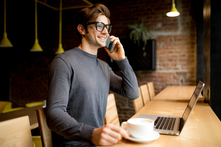 Photo pour Handsome young freelancer in eye glasses speak smartphone while on laptop - image libre de droit