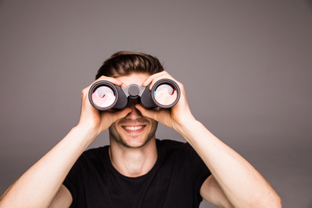 Photo for Young handsome man searching with binoculars near laptop at office work place - Royalty Free Image