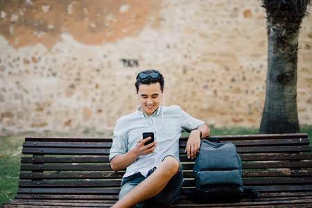 Photo for Profile of a happy guy using a smart phone sitting on a bench in a park - Royalty Free Image
