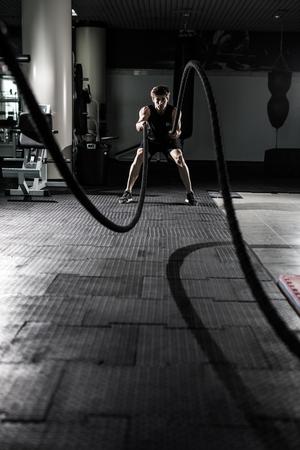 Foto de Crossfit battling ropes at gym workout exercise - Imagen libre de derechos
