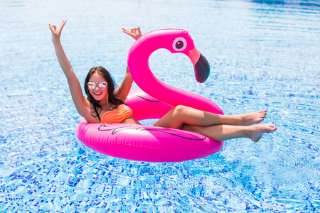 Foto de girl sits on inflatable mattress flamingos in the pool - Imagen libre de derechos