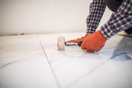 Photo for The workers hand is knocking rubber hammer on the tile for better gluing - Royalty Free Image