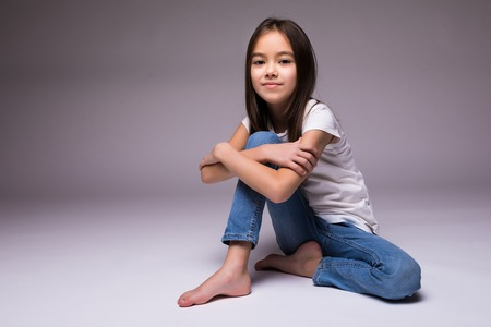 Foto de lovely little girl sitting on the floor, isolated on white background - Imagen libre de derechos