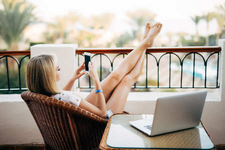 Photo for Woman using phone and relaxing at end of the day with feet up - Royalty Free Image