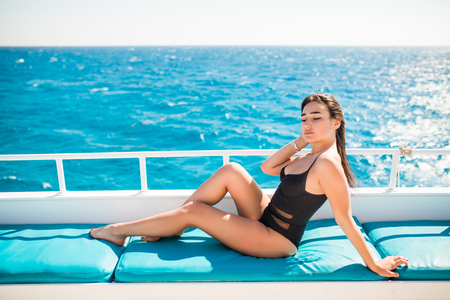 Photo for Beautiful woman smiling while lying on the deck of yacht - Royalty Free Image