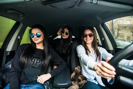 Photo for three girls driving in a convertible car and having fun - Royalty Free Image