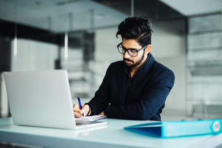 Photo for Cheerful young businessman writing in notebook on desk. - Royalty Free Image