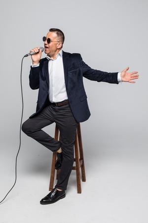 Photo for Portrait of senior man singing karaoke in white - Royalty Free Image
