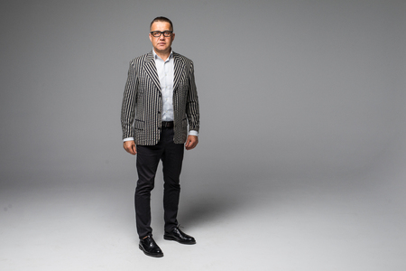 Foto de Portrait of a senior older business man standing wearing dark sunglasses on white background - Imagen libre de derechos