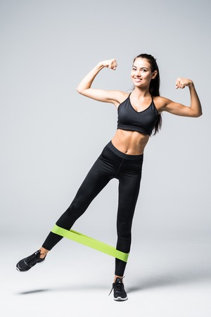 Photo pour Woman exercising doing workout for legs with elastic bands on white background - image libre de droit