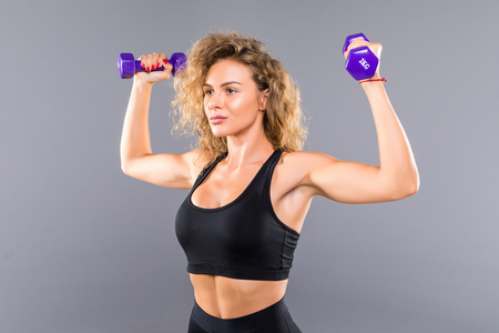 Foto per Photo of slim sporty woman doing exercises with small dumbbells isolated over gray background - Immagine Royalty Free