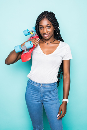 Foto de Portrait of african woman in trendy summer clothes and sunglasses with bright penny skateboard posing on blue background - Imagen libre de derechos