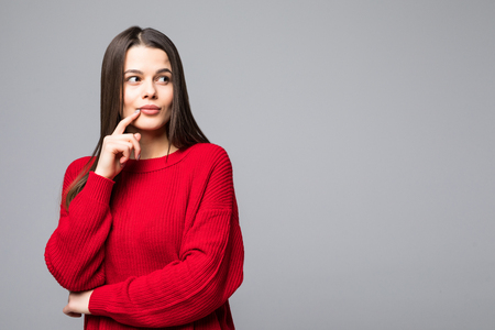 Photo pour Attractive young woman wearing casual clothes thinking, with finger on lips, looking at camera and standing isolated over white background. - image libre de droit