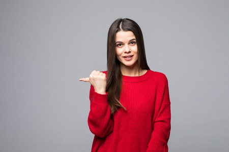 Photo for Shocked attractive girlfriend in trendy red sweater, pointing back on gray background - Royalty Free Image