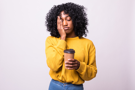 Foto für Only coffee may refresh me. Tired sleepy ethnic woman covers half of face with palm, has sad expression, closes eyes, carries disposable cup of drink containing caffeine, has continue working - Lizenzfreies Bild