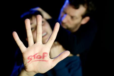 Foto de Man strangling young woman with stop sign on hand - Imagen libre de derechos
