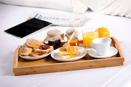 Photo for Breakfast tray laying on  bed in an hotel room - Royalty Free Image