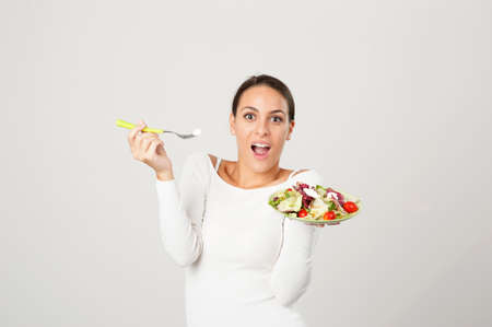 Photo pour woman eating salad against a white background - image libre de droit