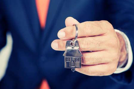 Foto de Estate agent giving house keys on a silver house shaped keychain - Imagen libre de derechos