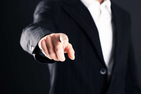 Photo for Business man pointing finger on dark background - Royalty Free Image