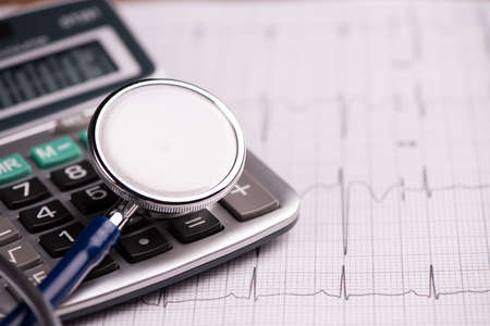 Foto de EKG with  stethoscope and calculator showing cost of health care. Close up - Imagen libre de derechos